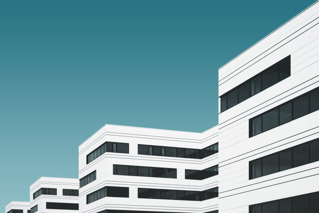 Image of white hospital and black windows.  You can report hospital fraud here.