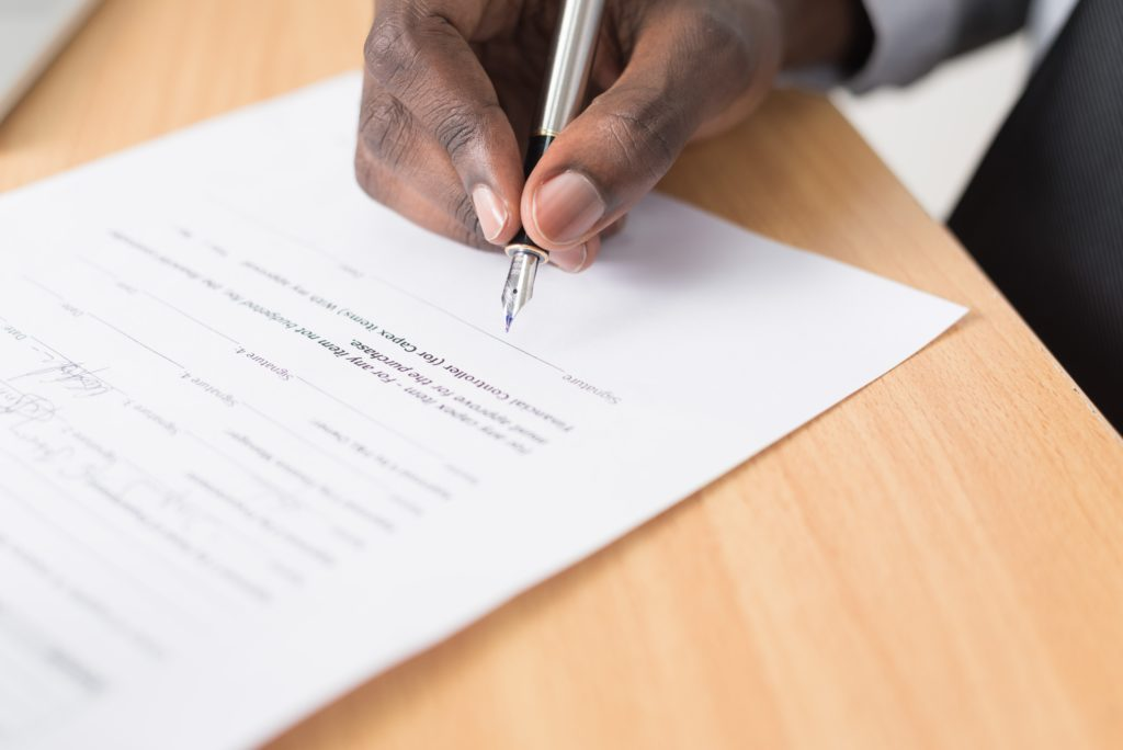 Hand holding pen, signing a contract - potentially a government contracting qui tam case.